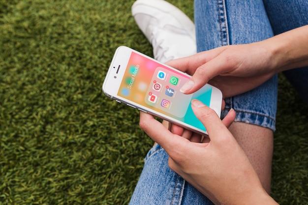 Nahaufnahme der hand der frau, die mobile mit social media-app auf schirm hält