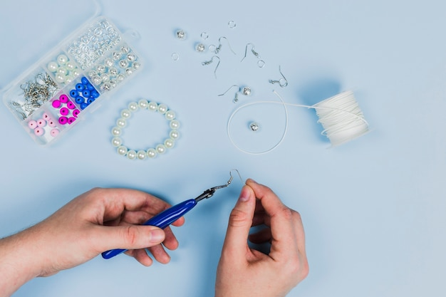 Nahaufnahme der hand der frau die ohrringe und das armband mit perlen auf blauem hintergrund machend