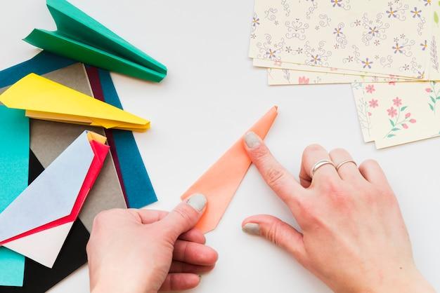 Nahaufnahme der hand der frau, die papierflugzeug mit bunten papieren auf weißem schreibtisch macht
