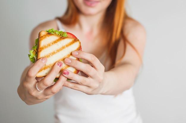 Nahaufnahme der hand der frau, die selbst gemachtes gegrilltes sandwich hält