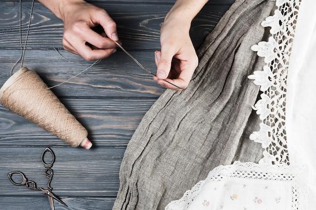 Nahaufnahme der hand der frau faden in nadel mit vielzahl des gewebes einfügend