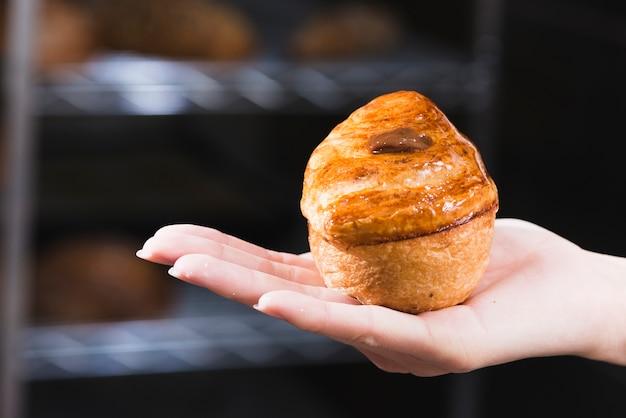 Nahaufnahme der hand der frau frisch gebackenen süßen blätterteig halten