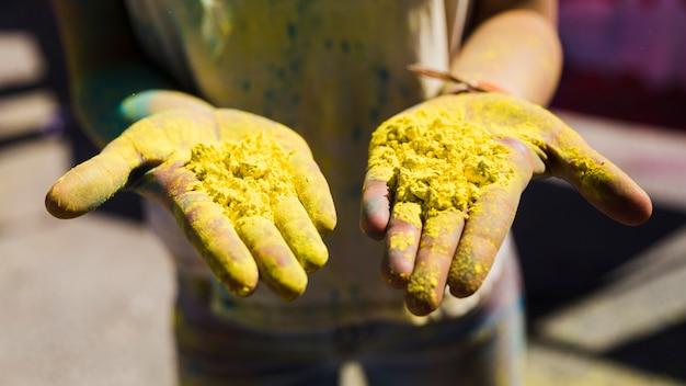 Nahaufnahme der hand der frau gelbe holi farbe zeigend