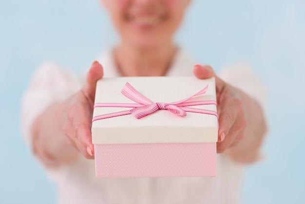 Nahaufnahme der hand der frau geschenkbox gebend