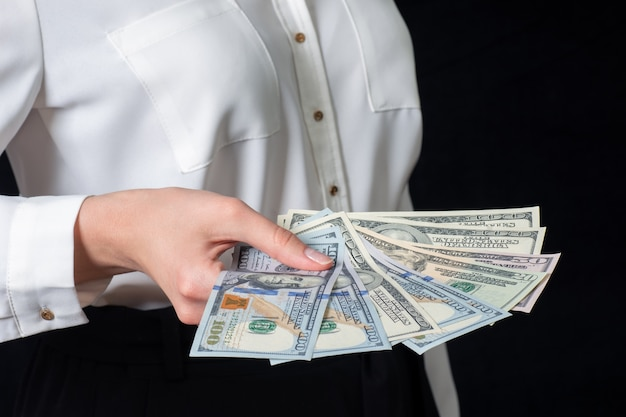 Nahaufnahme der hand der frau im weißen hemd, 100-dollar-banknoten haltend, lokalisiert auf schwarzem hintergrund. geschäftskonzept.