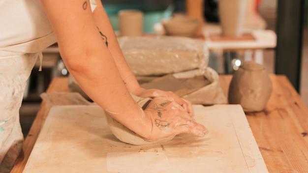 Nahaufnahme der hand der frau lehm auf dem brett knetend