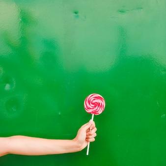 Nahaufnahme der hand der frau lollipop in der hand gegen grünen hintergrund halten