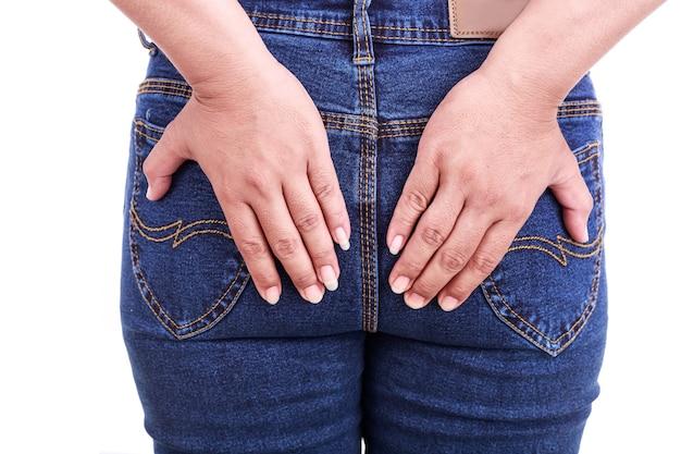 Nahaufnahme der hand der frau mit der rückseite: konzept hämorrhoiden