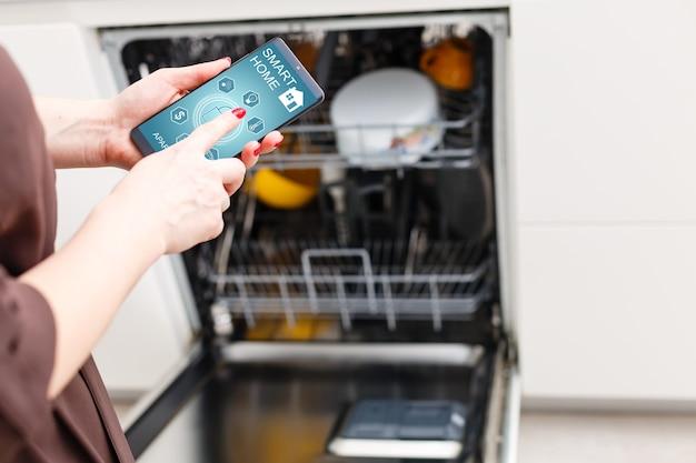 Nahaufnahme der hand der frau mit geschirrspüler-app auf dem handy in der küche