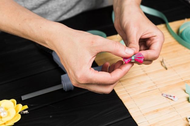 Nahaufnahme der hand der frau rosa haarspange halten
