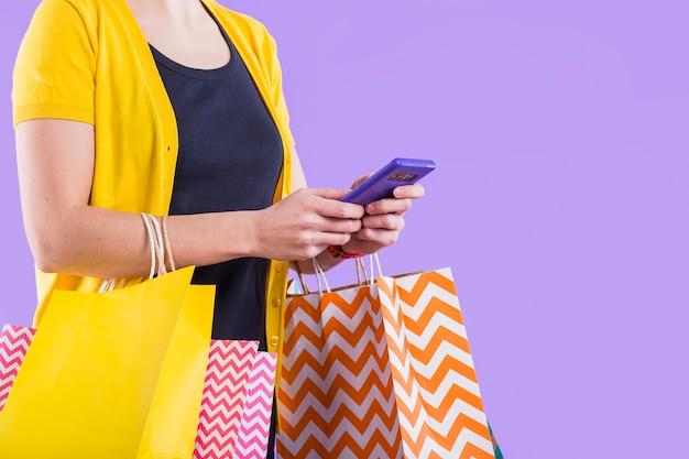 Nahaufnahme der hand der frau unter verwendung der weißen tragenden einkaufstasche des mobiltelefons