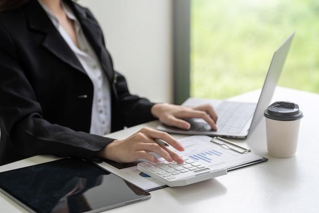 Nahaufnahme der hand der geschäftsfrau, die einen taschenrechner mit einem laptop verwendet, um im büro zu berechnen.