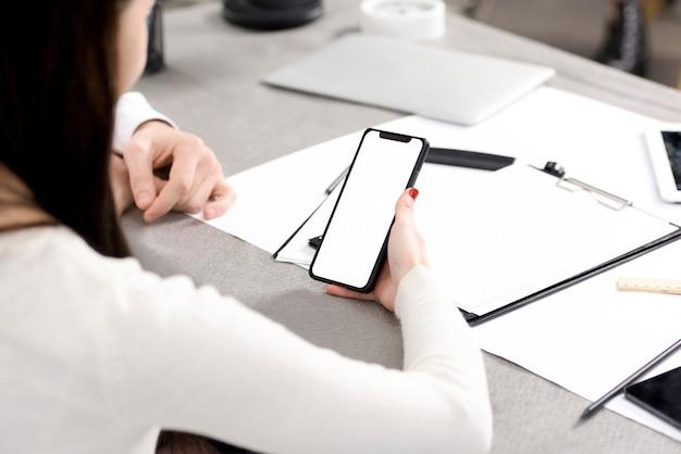 Nahaufnahme der hand der geschäftsfrau, die handy mit weißer bildschirmanzeige über dem schreibtisch hält