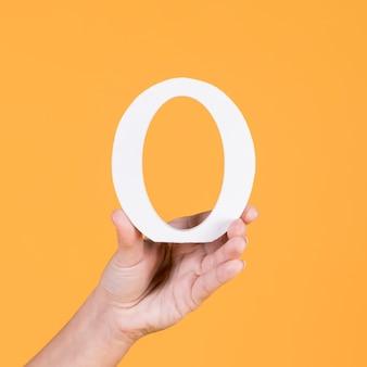 Nahaufnahme der hand der person alphabet des kapitals o halten