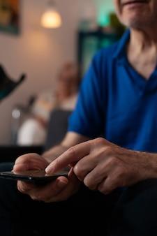 Nahaufnahme der hand des alten, reifen mannes, die mit moderner technologie mit online-internetverbindung auf dem bildschirm des smartphones tippt. ältere person, die zu hause sitzt und digitale kommunikation lernt