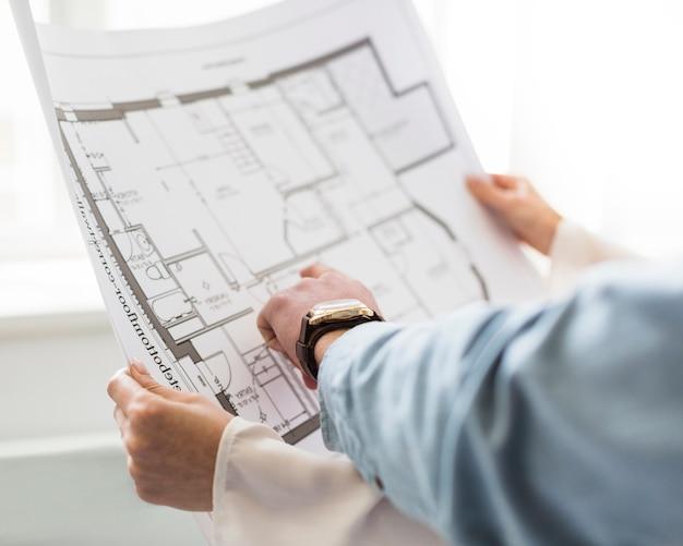 Nahaufnahme der hand des architekten, die plan auf plan bespricht