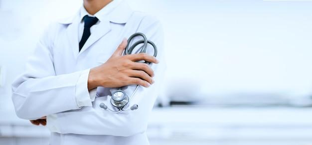 Nahaufnahme der hand des arztes, die stethoskop mit unscharfem hintergrund am krankenhaus hält