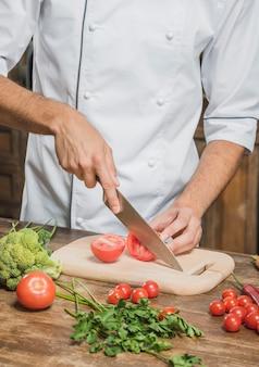 Nahaufnahme der hand des chefs, die rote tomate auf hackendem brett schneidet