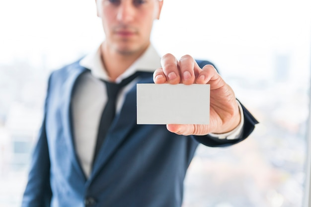Nahaufnahme der hand des geschäftsmannes leere visitenkarte zeigend