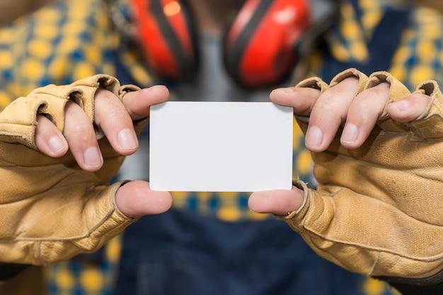 Nahaufnahme der hand des heimwerkers schutzhandschuhe zeigend, die visitenkarte zeigen