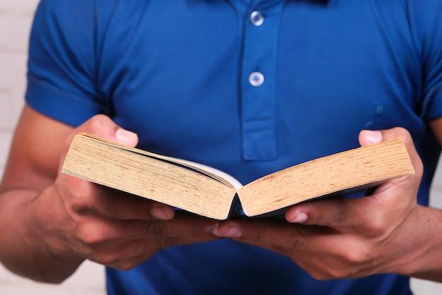Nahaufnahme der hand des jungen mannes, der ein buch liest