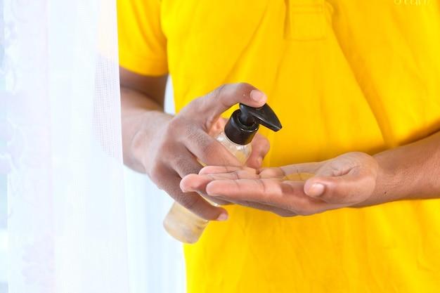 Nahaufnahme der hand des jungen mannes unter verwendung des desinfektionsgels zur verhinderung des virus.