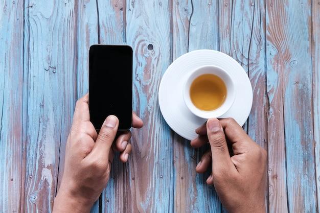 Nahaufnahme der hand des jungen mannes unter verwendung des smartphones.
