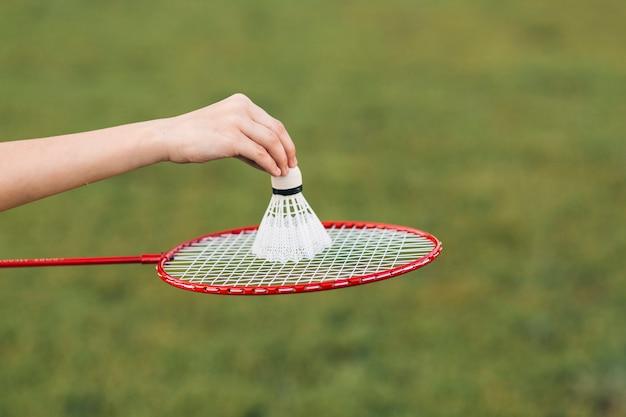 Nahaufnahme der hand des mädchens, die federball über badminton setzt