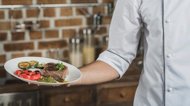 Nahaufnahme der hand des männlichen chefs, die in der hand gebratenen rindfleischteller hält