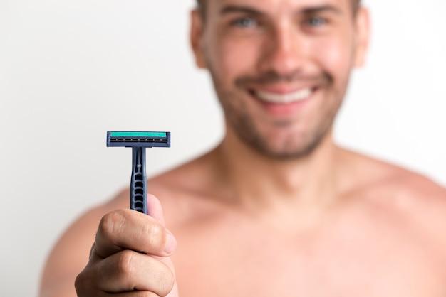 Nahaufnahme der hand des mannes blaues rasiermesser halten