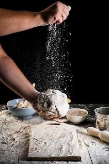 Nahaufnahme der hand des mannes das mehl auf dem teig spritzend