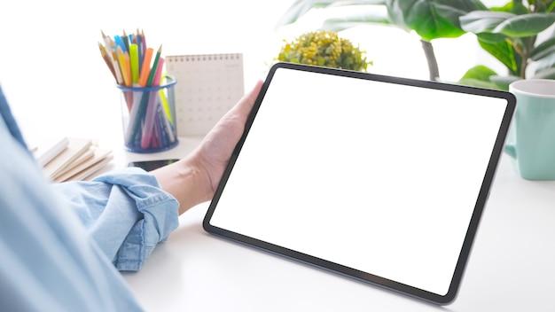 Nahaufnahme der hand des mannes, die digitales tablet mit schwarzem bildschirm auf arbeitstischhintergrund für mock-up, vorlage hält