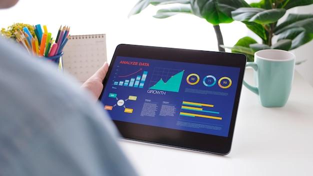 Nahaufnahme der hand des mannes, die ein digitales tablet mit geschäftsdatenanalyse im home office, geschäft und technologie hält, zu hause