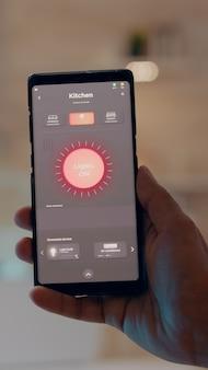 Nahaufnahme der hand des mannes, die ein telefon mit moderner software zur steuerung von lichtern hält