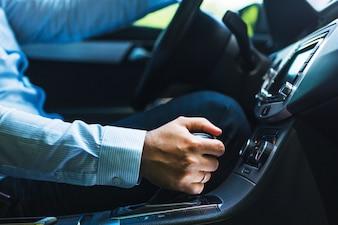 Nahaufnahme der Hand des Mannes, die Gang im Auto schiebt