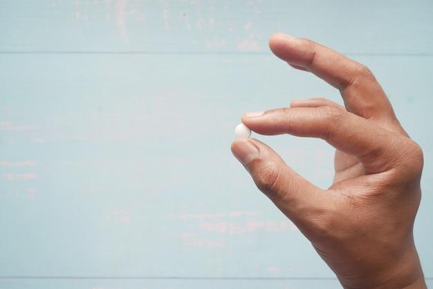 Nahaufnahme der hand des mannes, die pillen mit kopienraum hält