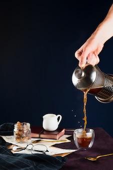 Nahaufnahme der hand des mannes, die schwarzen kaffee von der französischen presse in eine tasse auf einem holztisch mit gläsern, milchhalter, rohrzucker und notizbuch gießt, selektiver fokus