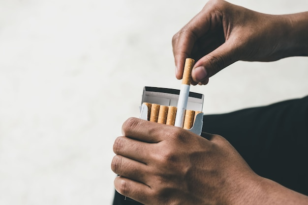 Nahaufnahme der hand des mannes, die sie von der zigarettenpackung abzieht, bereiten sie das rauchen einer zigarette vor. packen schlange. zigarettenrauch breitete sich aus.