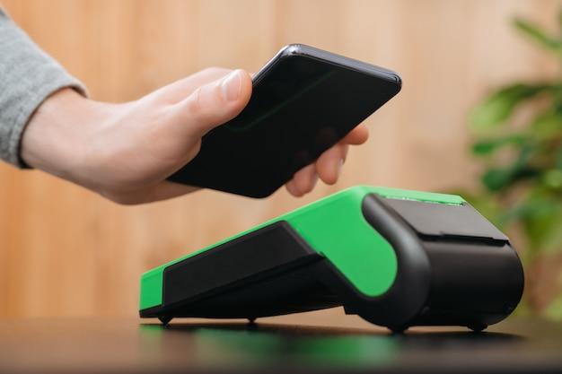 Nahaufnahme der hand des mannes, die smartphone nahe nfc zahlungsterminal hält