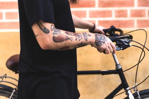 Nahaufnahme der hand des mannes mit der tätowierung, die fahrrad vor wand hält