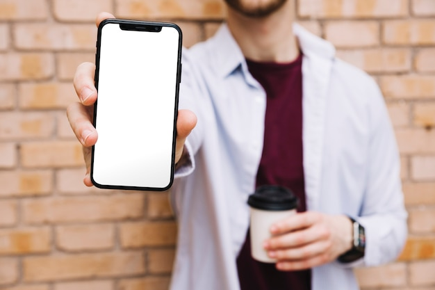 Nahaufnahme der hand des mannes smartphone mit leerem weißem schirm zeigend