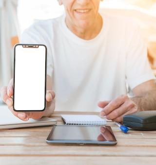 Nahaufnahme der hand des mannes smartphone mit weißem schirm zeigend