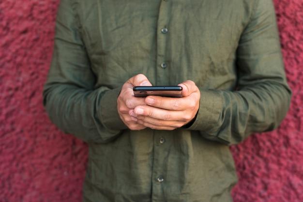 Nahaufnahme der hand des mannes unter verwendung des mobiltelefons