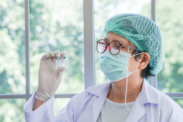 Nahaufnahme der hand des medizinischen personals der krankenschwester, das eine flasche impfstoff zeigt