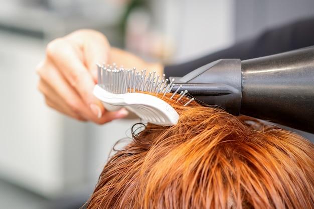 Nahaufnahme der hand des meisters mit föhnen und haarbürste weht weibliches rotes haar in einem salon.
