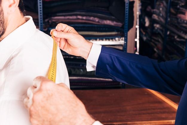 Nahaufnahme der hand des modedesigners, die maß nimmt
