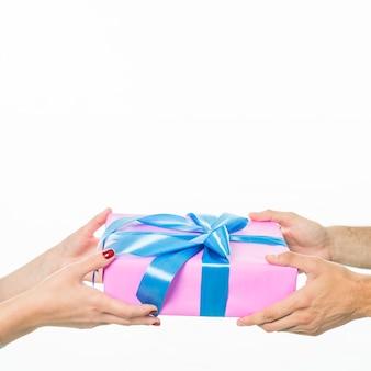 Nahaufnahme der hand des paares geschenkbox auf weißem hintergrund halten