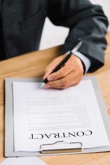 Nahaufnahme der hand des rechtsanwalts ein offizielles dokument unterzeichnend