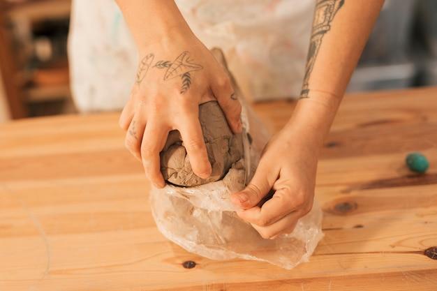 Nahaufnahme der hand des weiblichen töpfers den lehm vom plastikpapier auf holztisch entfernend