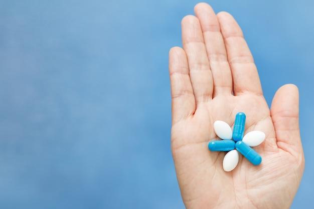 Nahaufnahme der hand, die blaue und weiße pillen in form einer blume hält. pillen auf der hand der frau